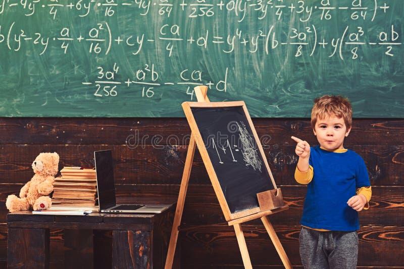 Weinig jongen met sluw gezicht die zich voor groene raad bevinden Leerling die op bord richten Kind het leren rekenkunde royalty-vrije stock foto's