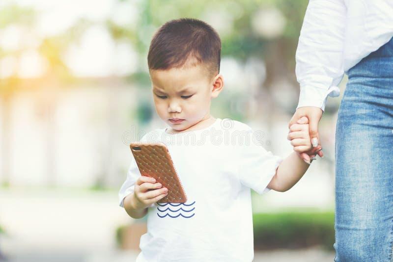 Weinig jongen met smartphone stock foto