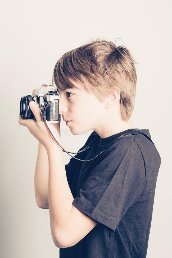 Weinig jongen met uitstekende reflexcamera stock foto