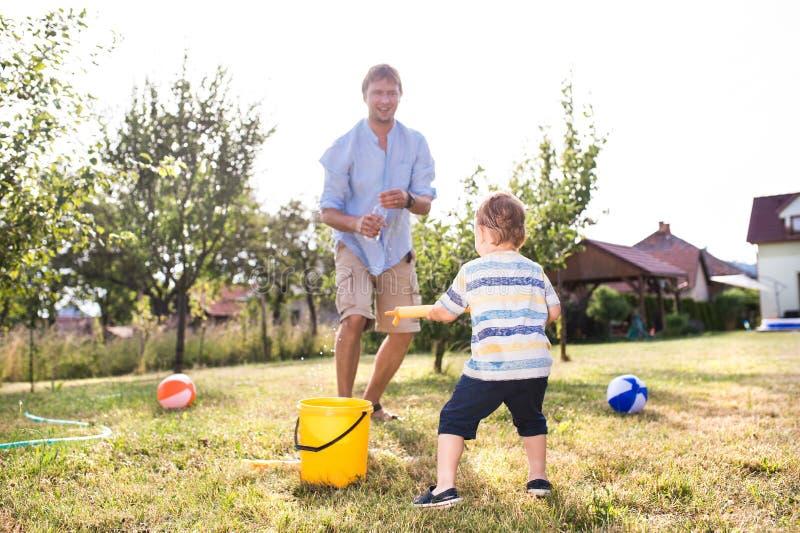 Weinig jongen met vader het spelen met waterkanonnen, het bespatten royalty-vrije stock fotografie