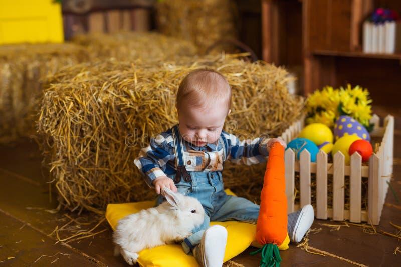 Weinig jongen met wit konijn spelen en wortel die binnen De pret van de lentepasen voor kinderen Gelukkig kinderjarenconcept stock foto