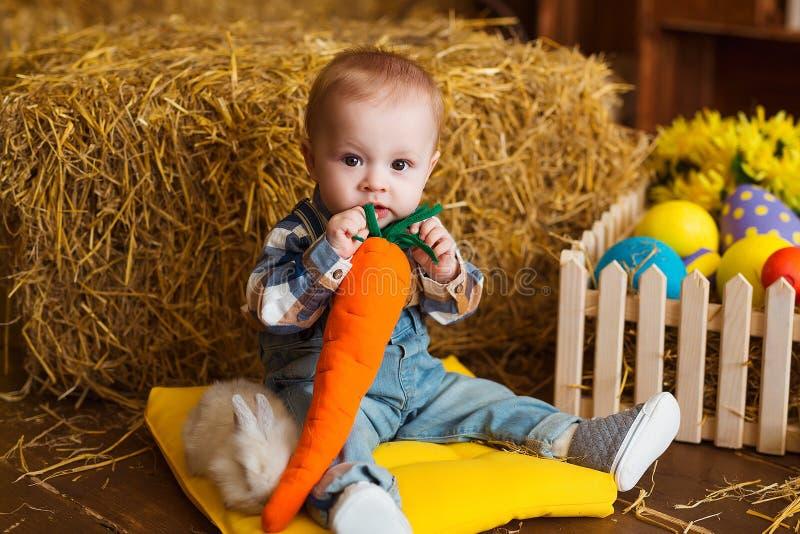 Weinig jongen met wit konijn spelen en wortel die binnen De pret van de lentepasen voor kinderen Gelukkig kinderjarenconcept stock fotografie