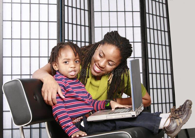 Weinig jongen met zijn mama en een PC royalty-vrije stock afbeelding
