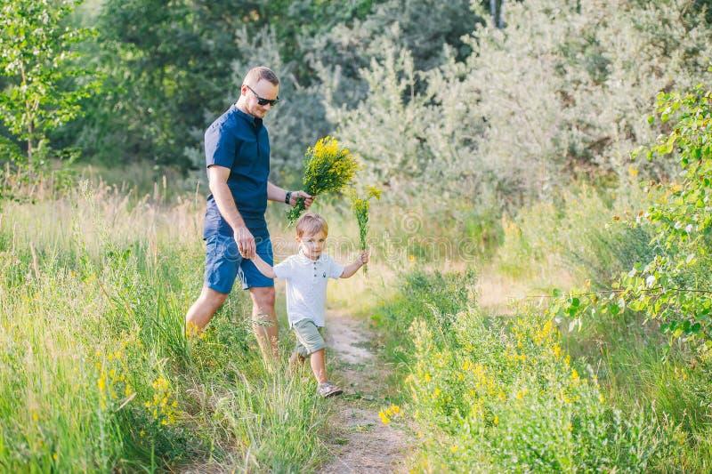 Weinig jongen met zijn vader verzamelt de zomerbloemen op de weide voor moeder stock foto