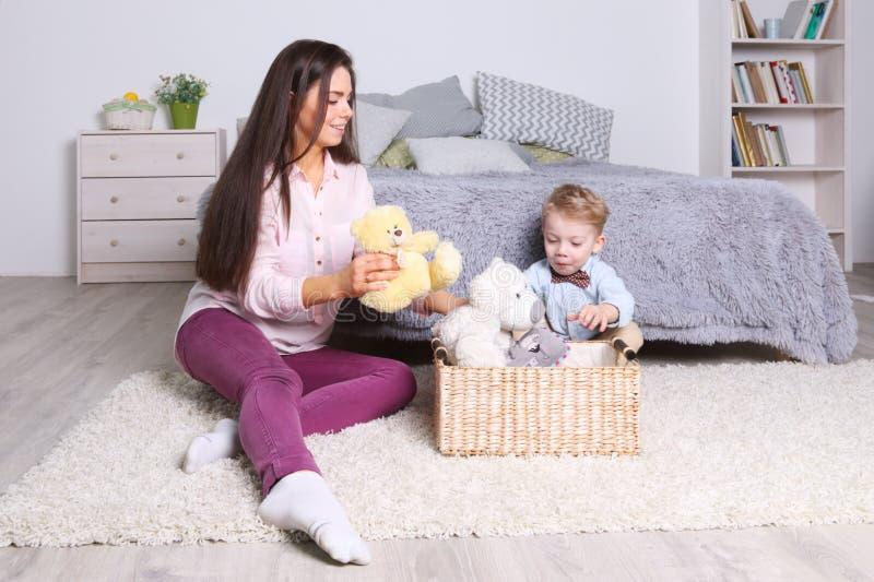 Weinig jongen, moederspel met speelgoed in mand in slaapkamer royalty-vrije stock fotografie