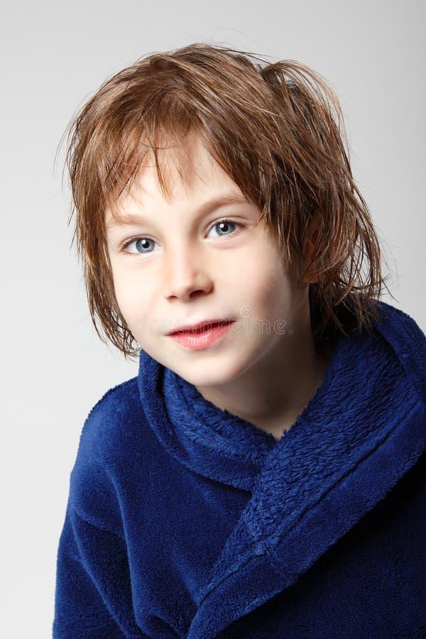 Weinig jongen mooi na douche in blauwe badjas met nat haar stock afbeelding