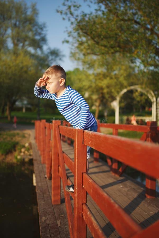 Weinig jongen onderzoekt de afstand stock afbeelding