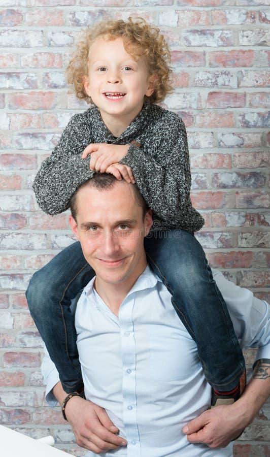 Weinig jongen op de schouders van zijn vader royalty-vrije stock foto