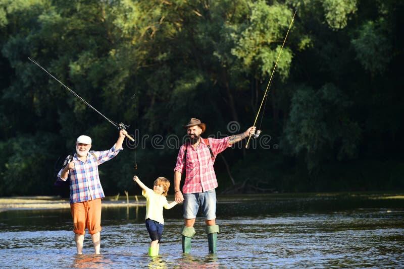 Weinig jongen op een meer met zijn vader en grootvader De zoons hoe te vlieg-vissen van het vaderonderwijs in rivier Gelukkige vi stock foto