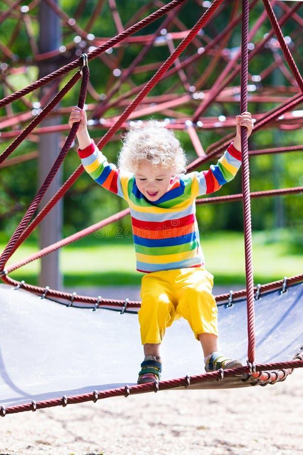 Weinig jongen op een speelplaats stock afbeelding
