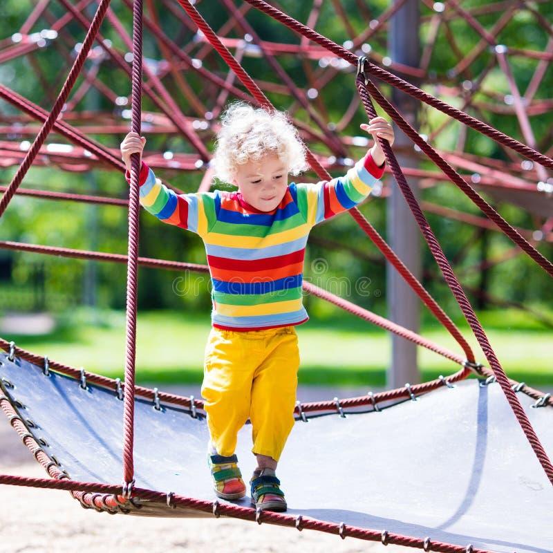 Weinig jongen op een speelplaats stock afbeeldingen
