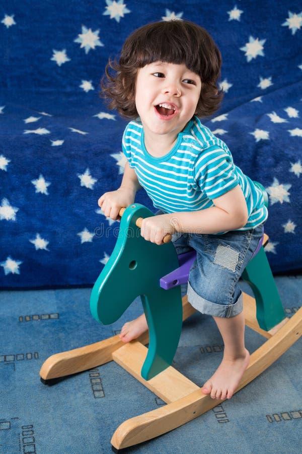 Weinig jongen op een stuk speelgoed paard in een ruimte stock afbeelding