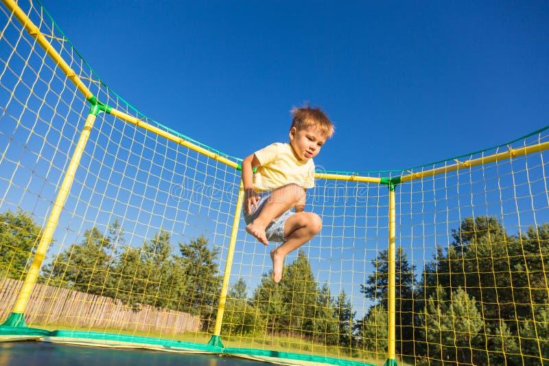 Weinig jongen op een trampoline stock afbeelding