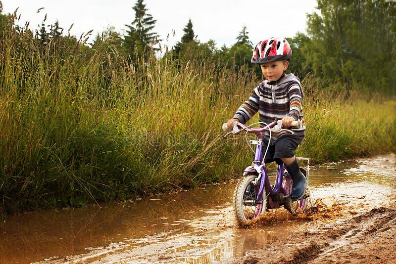 Weinig jongen op fiets stock afbeelding