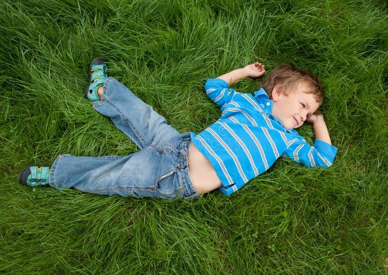 Weinig jongen op gras royalty-vrije stock afbeeldingen