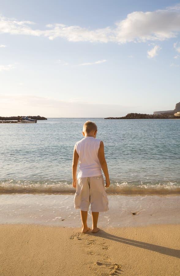Weinig jongen op het strand dat neer eruit ziet stock foto's