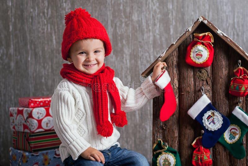 Weinig jongen op Kerstmis, het openen stelt voor stock foto's