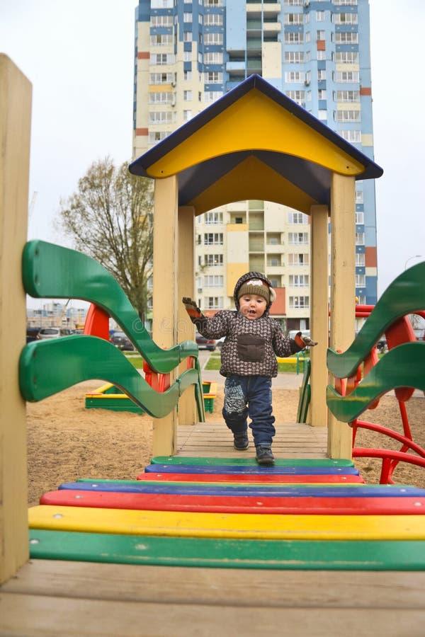 Weinig jongen op speelplaats in binnenplaats stock afbeelding