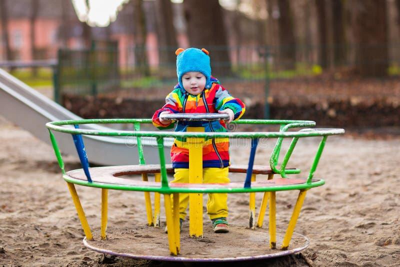Weinig jongen op speelplaats in de herfst stock fotografie