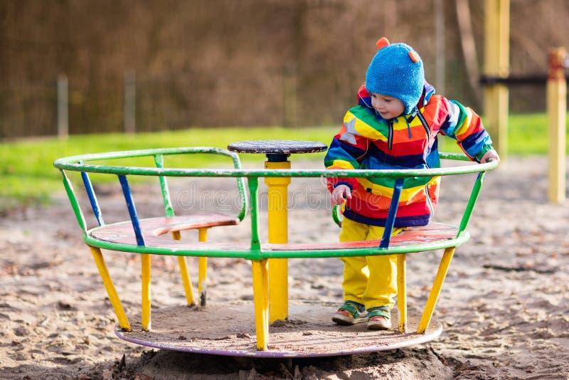 Weinig jongen op speelplaats in de herfst stock afbeeldingen