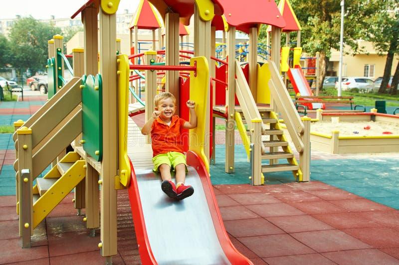Weinig jongen op speelplaats speelkind op dia stock fotografie
