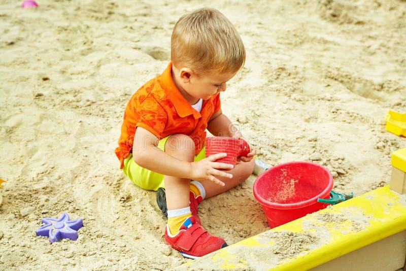 Weinig jongen op speelplaats speelkind in zandbak stock foto