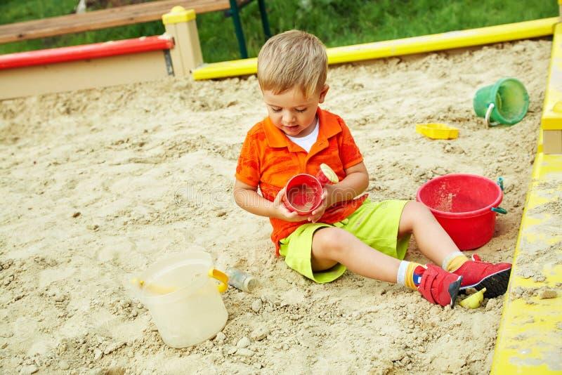 Weinig jongen op speelplaats speelkind in zandbak royalty-vrije stock foto