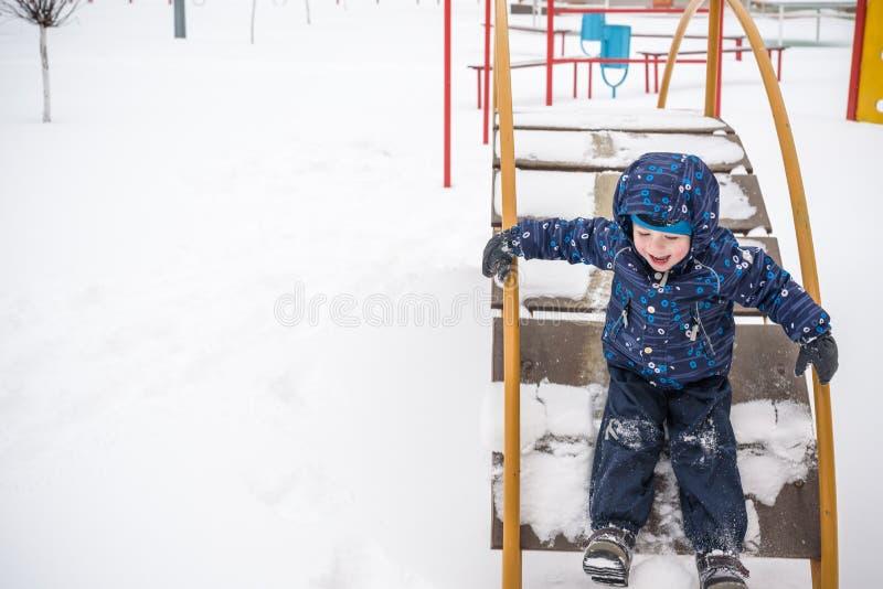 Weinig jongen in openlucht in koude de wintersneeuw speelplaats stock foto's