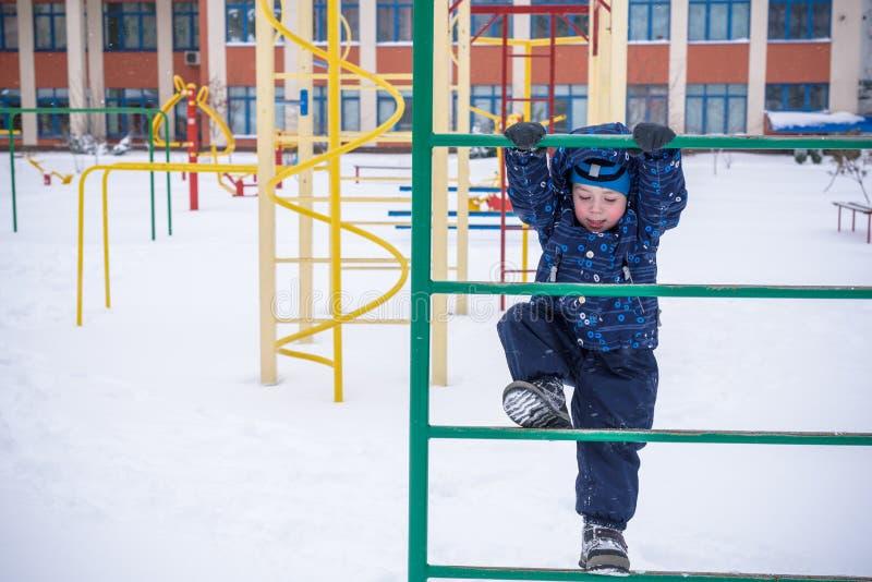 Weinig jongen in openlucht in koude de wintersneeuw speelplaats stock foto