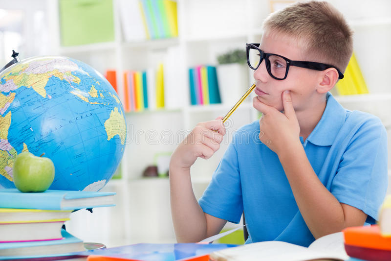 Weinig jongen over de wereld bestuderen, en thinkig iets die stock fotografie