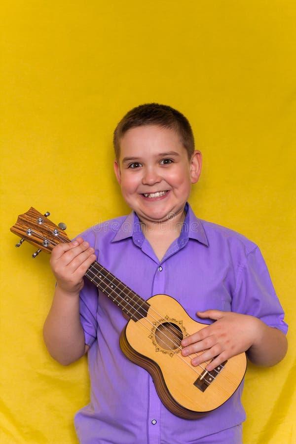 Weinig jongen in overhemdsspelen op Hawaiiaanse gitaar of ukelele iolated op gele achtergrond stock foto's