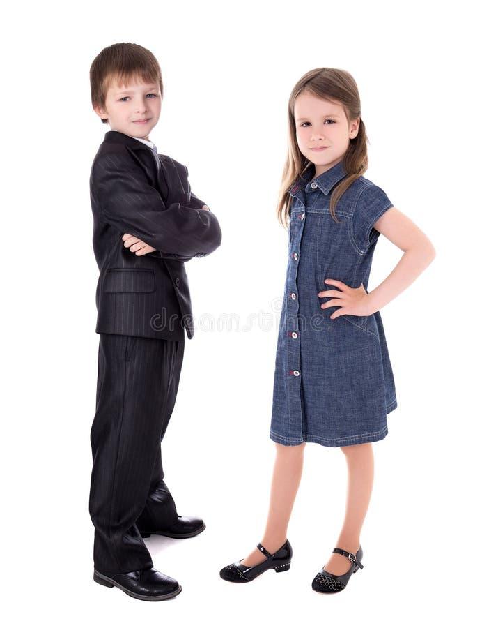 Weinig jongen in pak en meisje in kleding dat op wit wordt geïsoleerd stock afbeeldingen