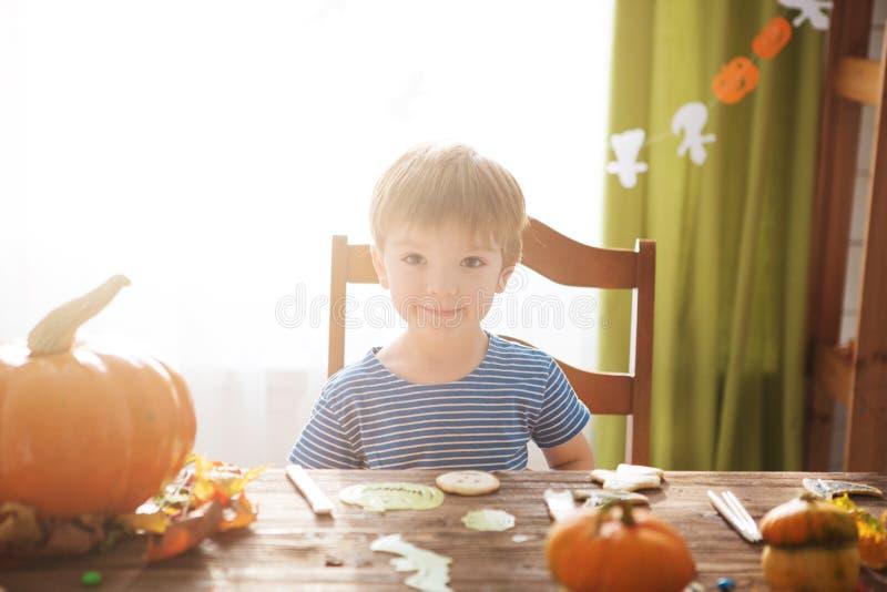 Weinig jongen in piraatkostuum op Halloween-truc of behandelt Jonge geitjes die pompoenlantaarn snijden De kinderen vieren Hallow royalty-vrije stock fotografie