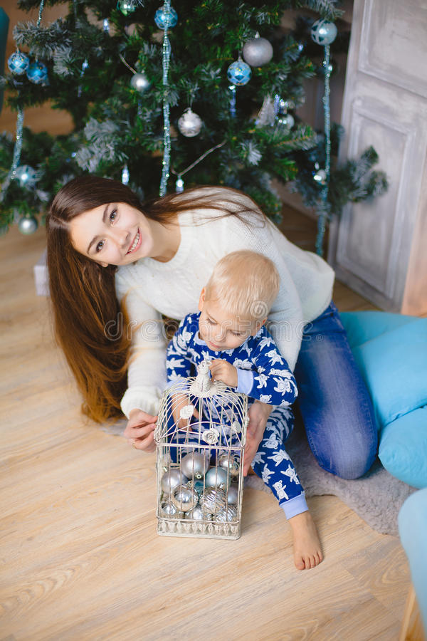 Weinig jongen in pyjama's zit en glimlacht met zijn zuster dichtbij Kerstmisboom stock foto