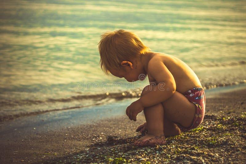 Weinig jongen in rode borrels speelde op het strand stock foto's