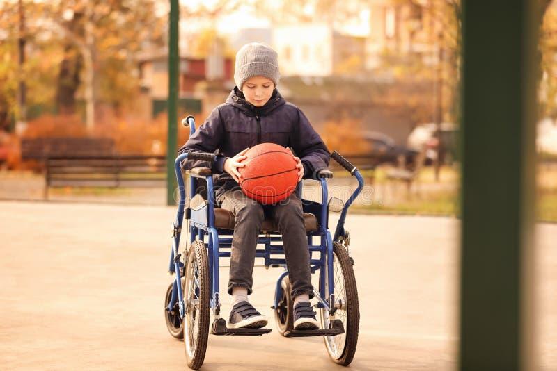 Weinig jongen in rolstoel met bal stock foto