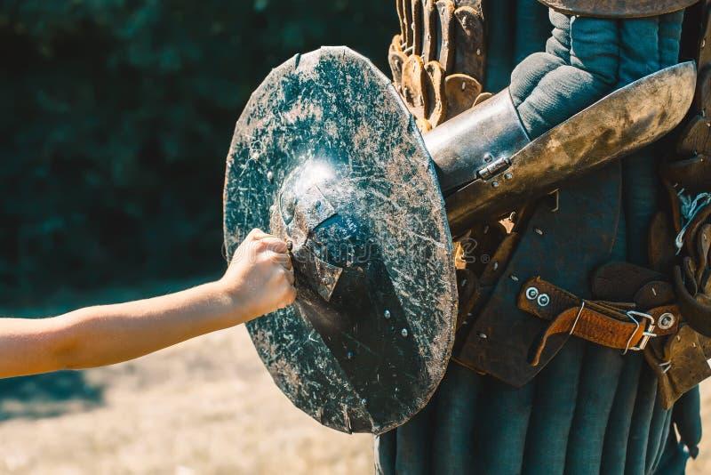 Weinig jongen rust zijn versleten vuist op de gekneuste ridder, gebarsten, stock afbeelding