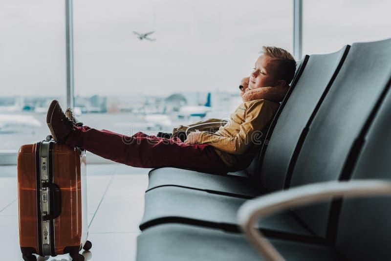 Weinig jongen slaapt in hal vóór vlucht royalty-vrije stock afbeelding