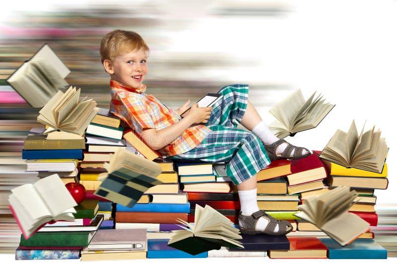 Weinig jongen, Snel Internet en een stapel van boeken stock foto
