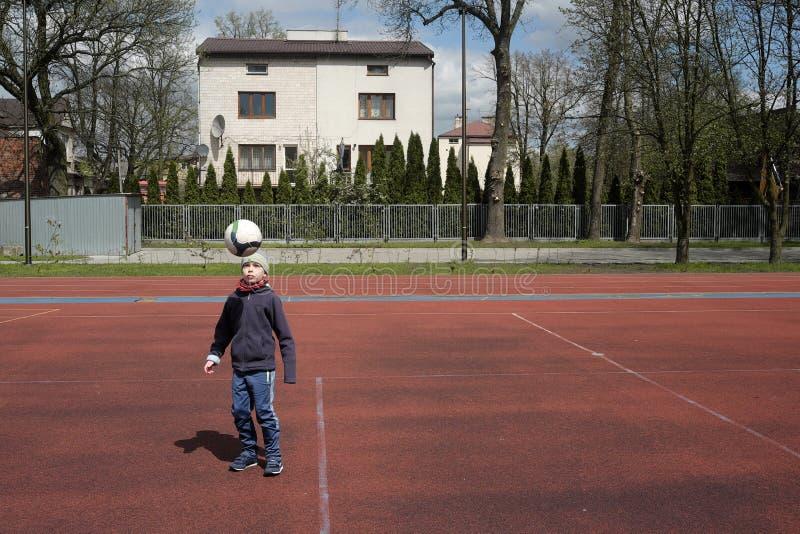 Weinig jongen speelt bal stock fotografie