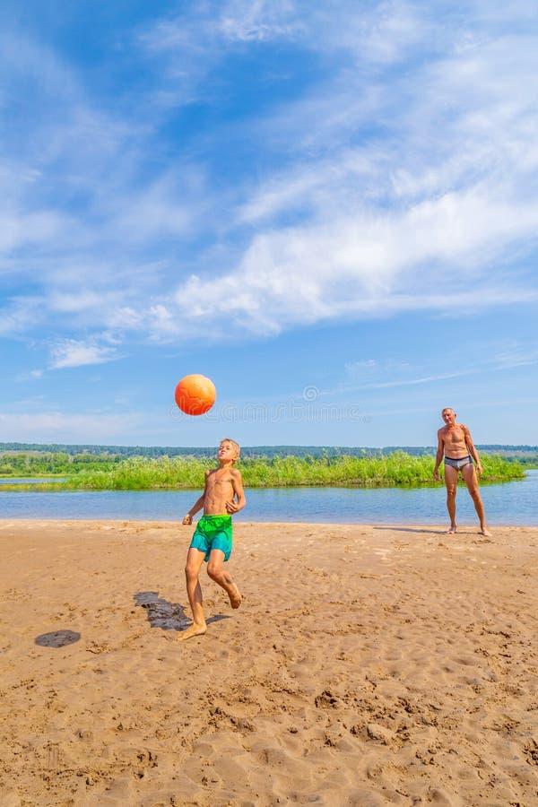 Weinig jongen speelt bal op het strand stock fotografie