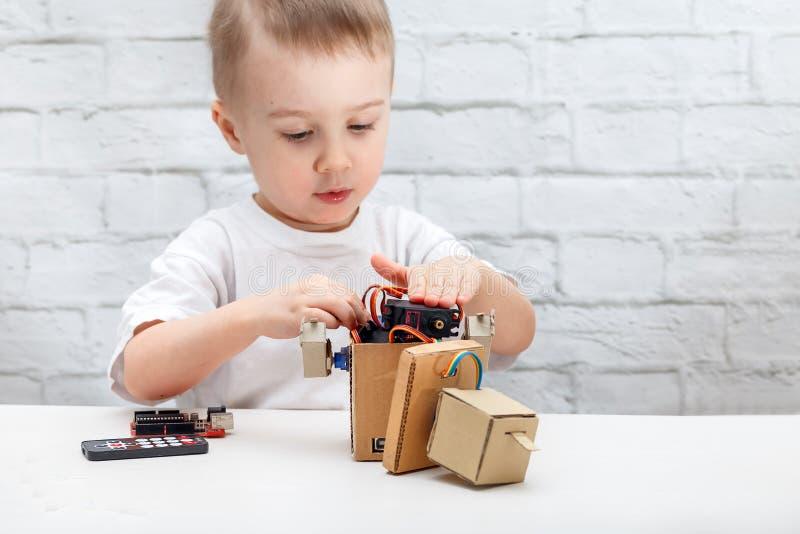 Weinig jongen speelt met de robot Het kind verzamelt een robotzitting bij de lijst stock fotografie