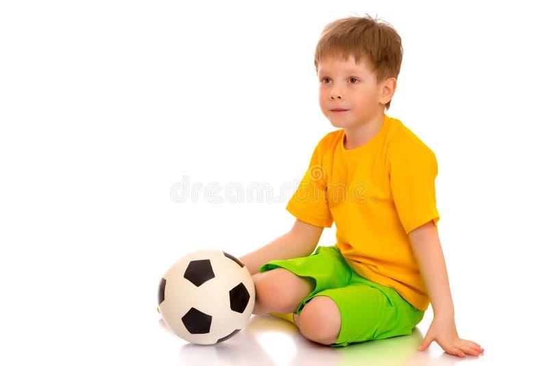 Weinig jongen speelt met een voetbalbal royalty-vrije stock foto's