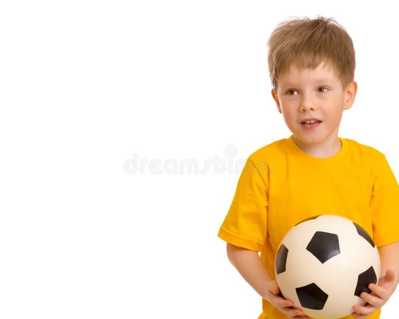 Weinig jongen speelt met een voetbalbal royalty-vrije stock afbeeldingen