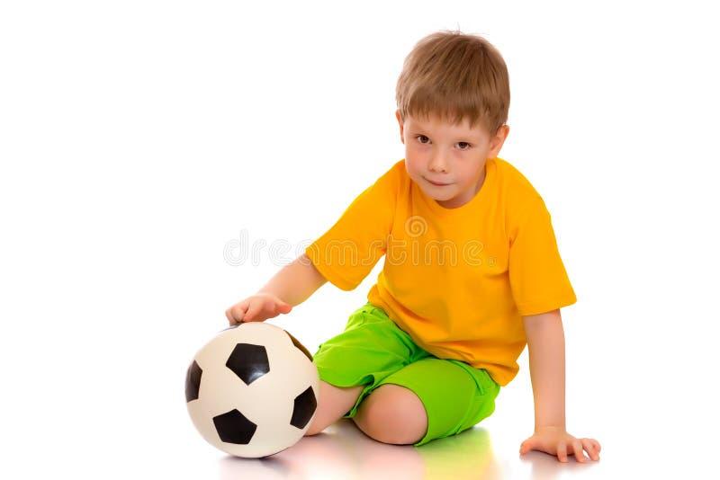 Weinig jongen speelt met een voetbalbal stock foto's