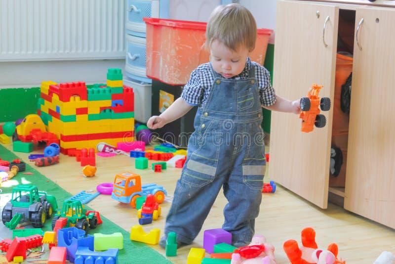 Weinig jongen speelt met stuk speelgoed auto's Kind onder het speelgoed in de soort royalty-vrije stock afbeeldingen