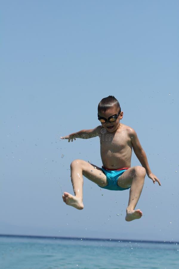 Weinig jongen springt in overzees stock fotografie