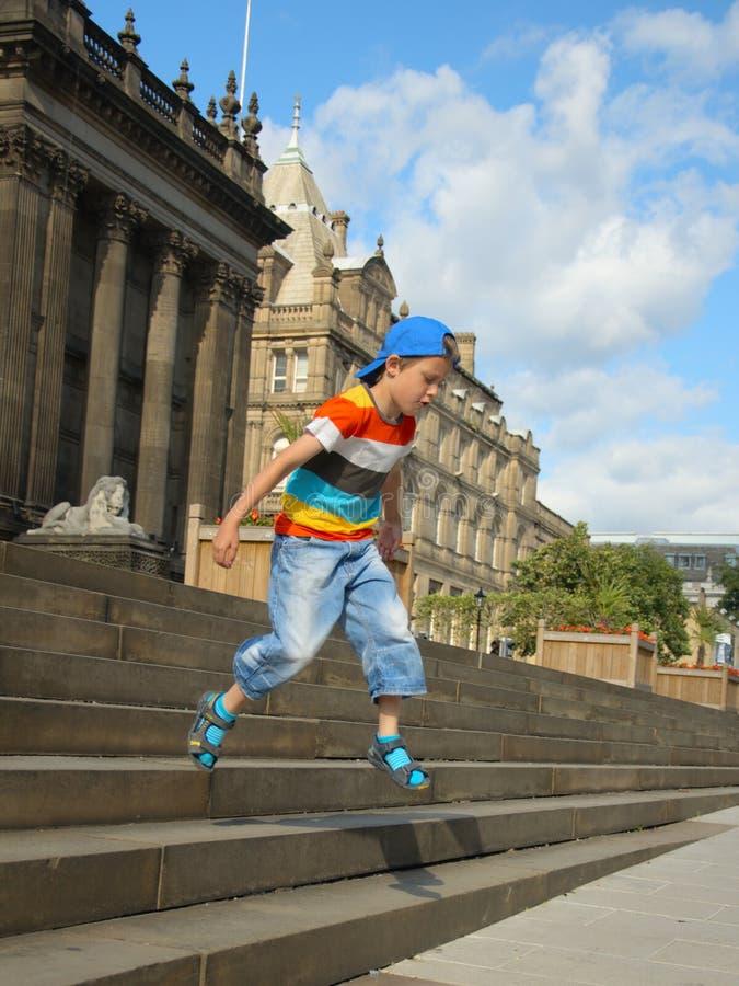 Weinig jongen springt van townhallstappen royalty-vrije stock afbeeldingen