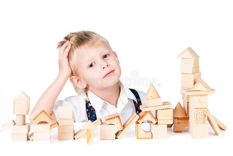 Weinig jongen stapelt huis van houten blokken isoleert royalty-vrije stock fotografie