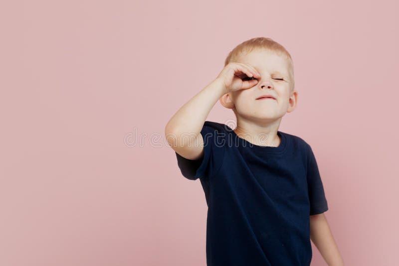 Weinig jongen in t-shirt, die de afstand onderzoeken De hand is als een telescoop Vooruit het loensen en het kijken stock foto's